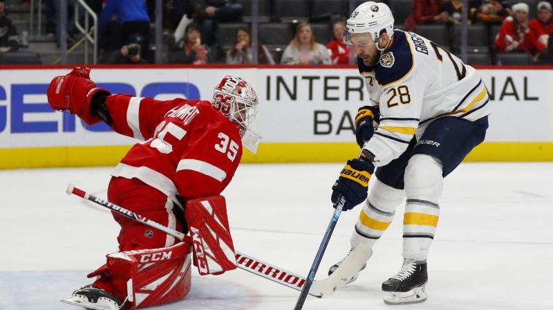 """Zemgus Girgensons apspēlē Detroitas """"Red Wings"""" vārtsargu Timu Hovardu. Foto: Paul Sancya/AP/Scanpix"""